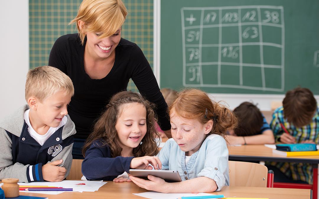Lehrerin hilft Schülern, die ein Tablet benutzen (Foto: contrastwerkstatt – stock.adobe.com)