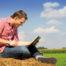 Mann mit Laptop sitzend in der Landschaft.
