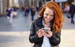 Eine Frau schaut auf ihr Smartphone. Bild: Adobe Stock