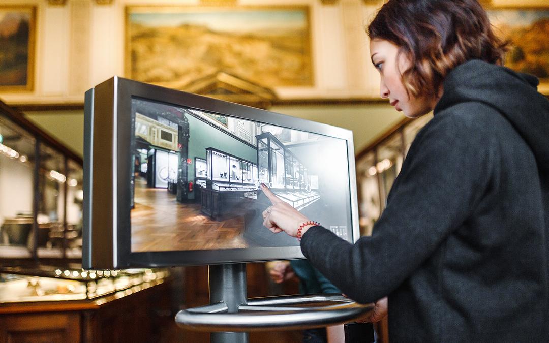 Eine junge Frau klickt in einem Museum auf das Display eines Bildschirms. (Foto: EdNurg – stock.adobe.com)