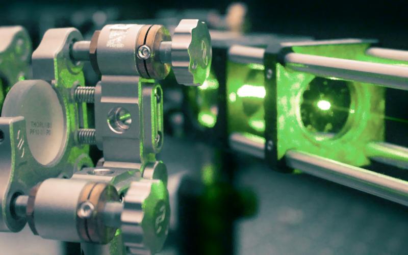Zu sehen ist eine Maschine mit grünem Photonenstrahl